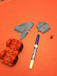 Broken Spaghetti, Snip and Paste Pieces, Pony Bead, Expo marker, and Lego Car